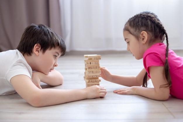 Twee kinderen spelen een spelletje jenga op de vloer Premium Foto