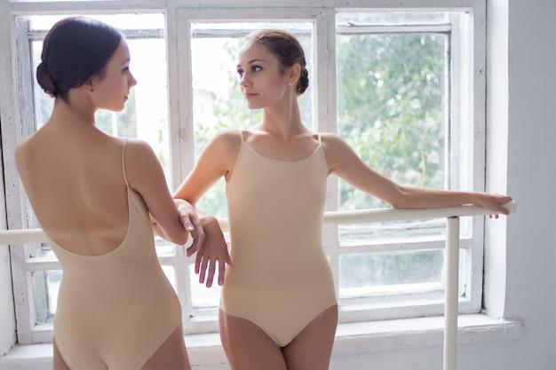 Twee klassieke balletdansers poseren op barre Gratis Foto