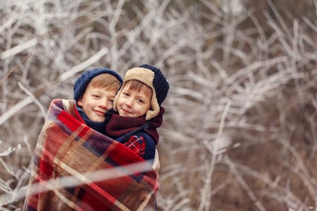 Twee kleine jongensvrienden koesteren onder warme deken in de winterbos. . broerderliefde. concept vriendschap Premium Foto