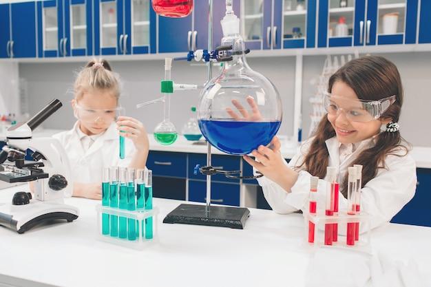 Twee kleine kinderen in laboratoriumjas het leren van chemie in schoollaboratorium. jonge wetenschappers die in beschermende bril experimenteren in laboratorium of chemisch kabinet. ingrediënten bestuderen voor experimenten. Premium Foto
