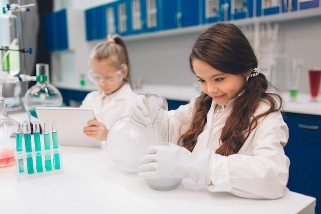 Twee kleine kinderen in laboratoriumjas het leren van chemie in schoollaboratorium. jonge wetenschappers die in beschermende bril experimenteren in laboratorium of chemisch kabinet. werken op een tablet. Premium Foto