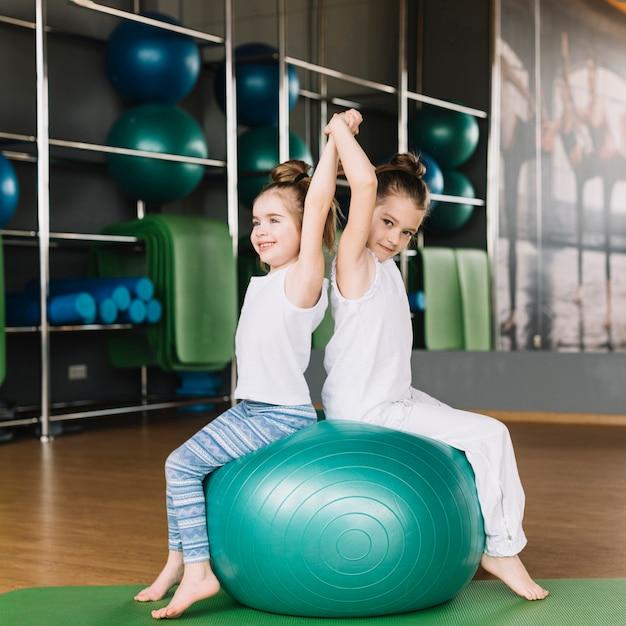 Twee kleine meisje zitten rug aan rug bij het samen oefenen van de bal Gratis Foto