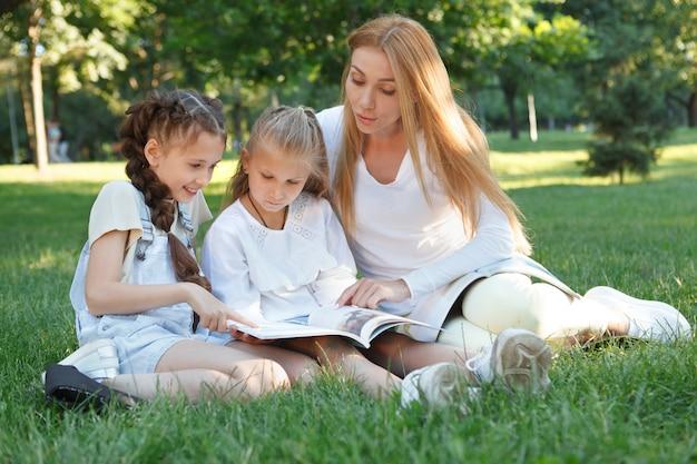 Twee kleine meisjes die genieten van openluchtles in het park met hun favoriete leraar Premium Foto