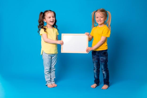 Twee kleine meisjes lachend met een lege tekentafel op een blauwe achtergrond Premium Foto