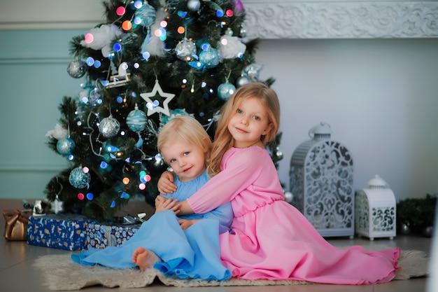 Twee kleine meisjes naast de kerstboom Premium Foto