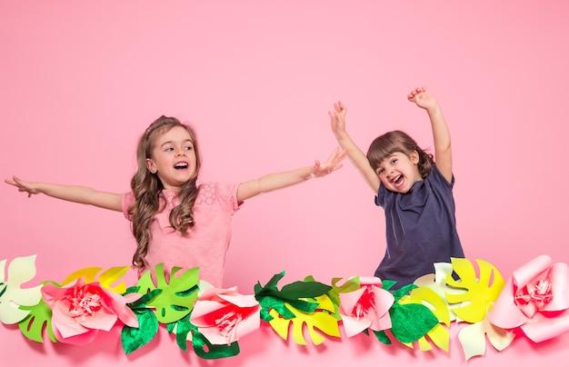 Twee kleine meisjes op zomer roze muur Gratis Foto