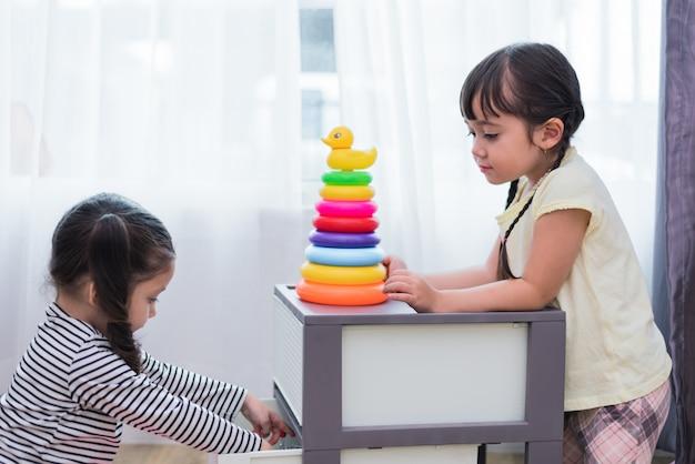 Twee kleine meisjes spelen kleine speelgoed ballen in huis samen. onderwijs en gelukslevensstijl Premium Foto