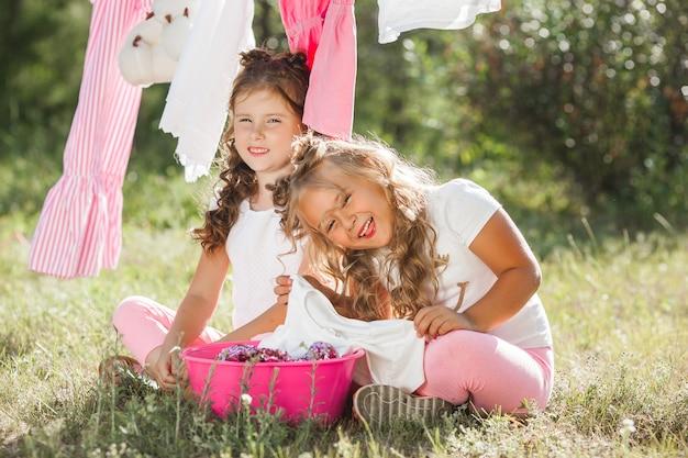 Twee kleine meisjes wassen. zusters die huishoudelijk werk doen Premium Foto