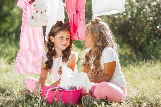 Twee kleine meisjes wassen. zusters doen huishoudelijk werk Premium Foto