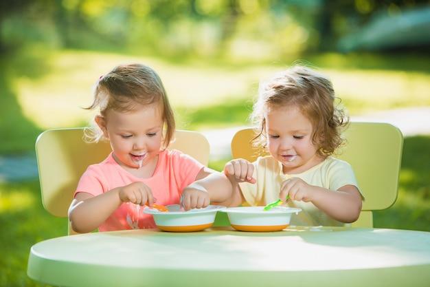 Twee kleine meisjes zitten aan een tafel en samen eten tegen groen gazon Gratis Foto