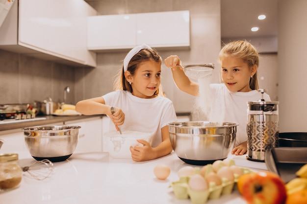Twee kleine meisjes zusjes koken in de keuken Gratis Foto