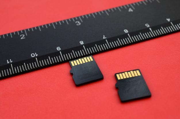 Twee kleine micro sd-geheugenkaarten liggen op een rode achtergrond Premium Foto