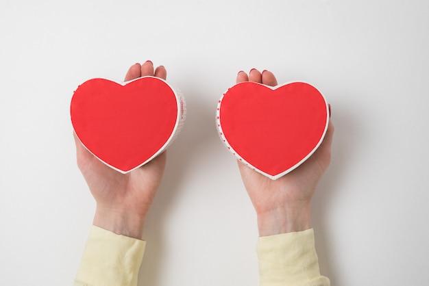 Twee kleine rode hartvormige dozen op vrouwelijke palmen op witte achtergrond. cadeau voor valentijnsdag Premium Foto