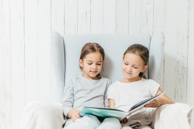 Twee kleine schattige zusjes zitten op de bank, lezen interessant boek, zitten op een comfortabele bank Premium Foto