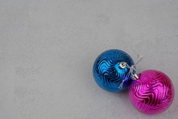 Twee kleurrijke kerstballen op grijze muur. Gratis Foto