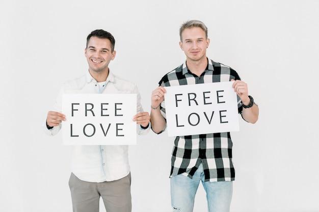 Twee knappe blanke mannen lgbt-activisten die strijden tegen homoseksuele discriminatie, vrije gelijke liefde, met posters met slogans Premium Foto