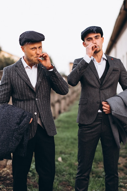 Twee knappe mannen in pak roken op de boerderij Gratis Foto
