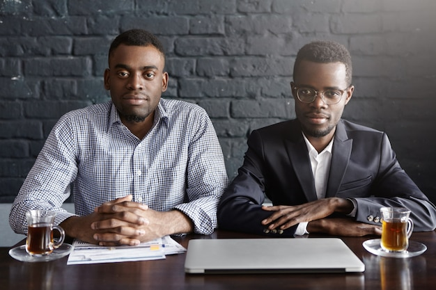 Twee knappe succesvolle afro-amerikaanse zakenlieden werken in kantoor zitten aan tafel met laptop, papieren en mokken Gratis Foto