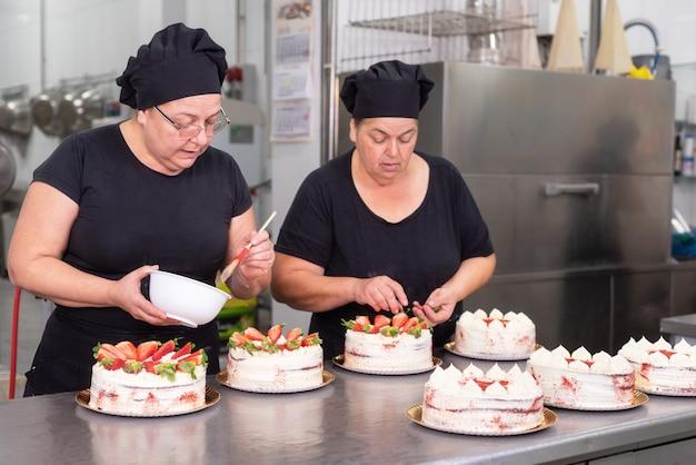 Twee koks die van het vrouwengebakje samen het maken van cakes werken bij de patisserie. Premium Foto