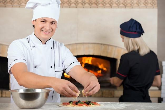 Twee koks, man en vrouw zijn aan het werk in een pizzeria. Premium Foto