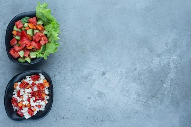 Twee kommen herderssalade naast een kom peper- en bloemkoolsalade op marmer. Gratis Foto