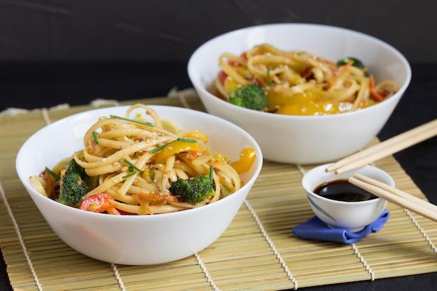 Twee kommen noedels met groenten en sojasaus op een bamboemat Premium Foto