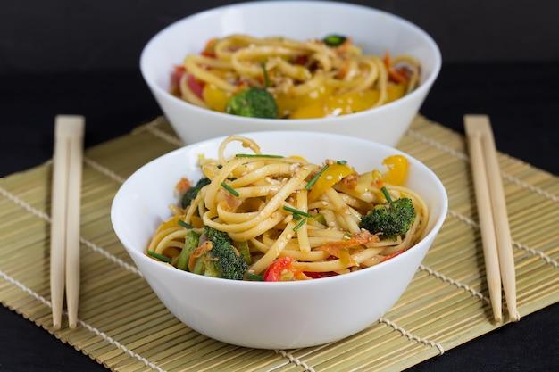 Twee kommen roerbak noedels met groenten en sojasaus op een bamboemat Premium Foto