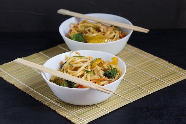 Twee kommen roerbak udonnoedels met groenten en sojasaus op een bamboemat Premium Foto