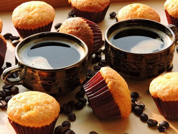 Twee kopjes espresso, mini-muffins, koffiebonen. Premium Foto