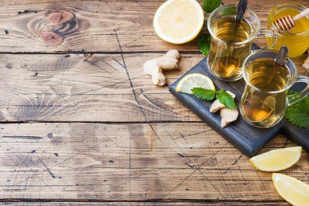 Twee kopjes natuurlijke kruidenthee gember citroen munt en honing op een houten oppervlak. Premium Foto