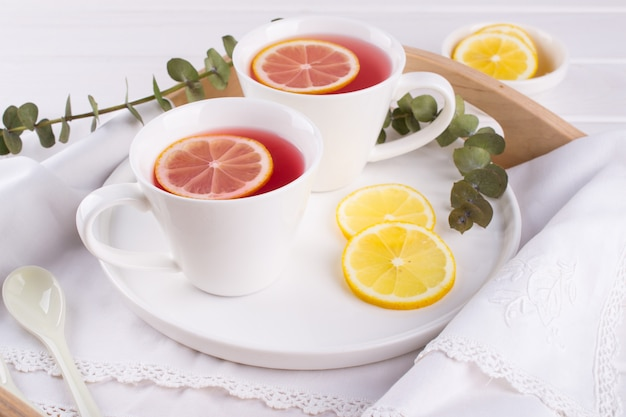 Twee kopjes rood fruit en kruidenthee met schijfje citroen, bovenaanzicht Premium Foto