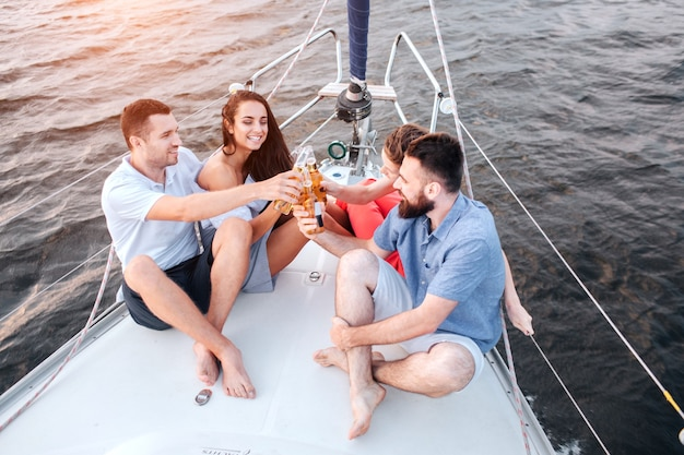 Twee koppels zittend op de boeg van een jacht en proost met bier Premium Foto