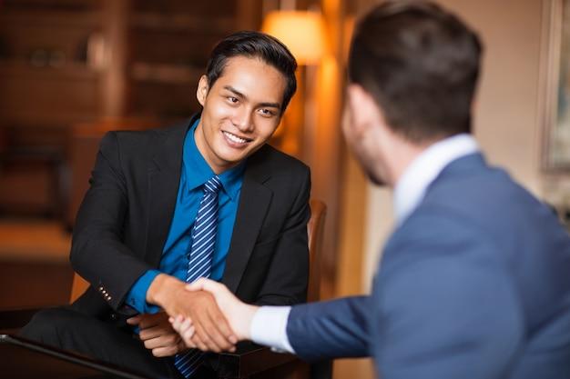 Twee lachende zakelijke partners schudden handen Gratis Foto
