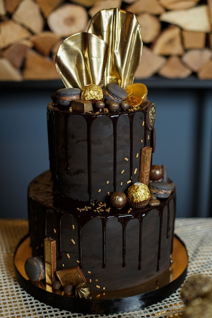 Twee lagen zwarte chocoladetaart versierd met gouden snoepjes op een achtergrond verjaardagstaart Premium Foto
