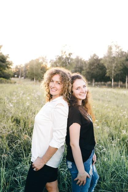 Twee lesbische meisjes staan met hun rug naar elkaar toe op het gras in het park. liefde van hetzelfde geslacht. lgbt-mensen Premium Foto