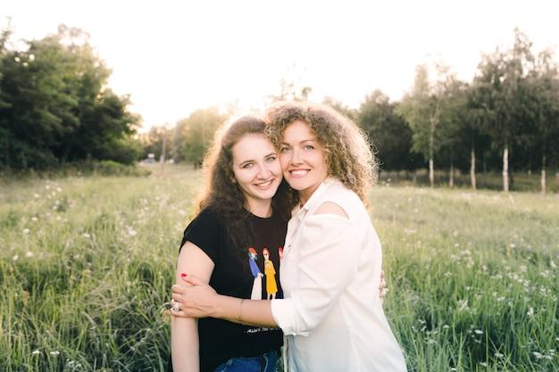 Twee lesbische meisjes zitten op het gras in het park en knuffelen elkaar. liefde van hetzelfde geslacht. lgbt-mensen Premium Foto