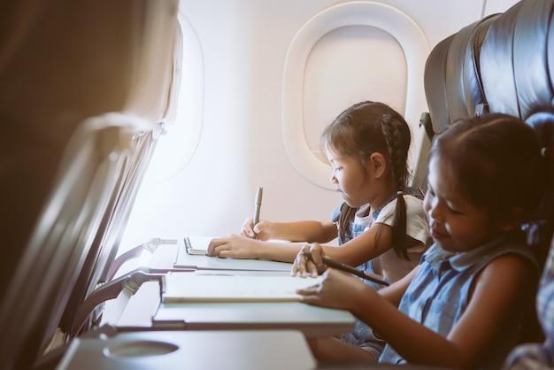 Twee leuke aziatische kindmeisjes die door een vliegtuig reizen en tijd door te trekken en te lezen doorbrengen Premium Foto