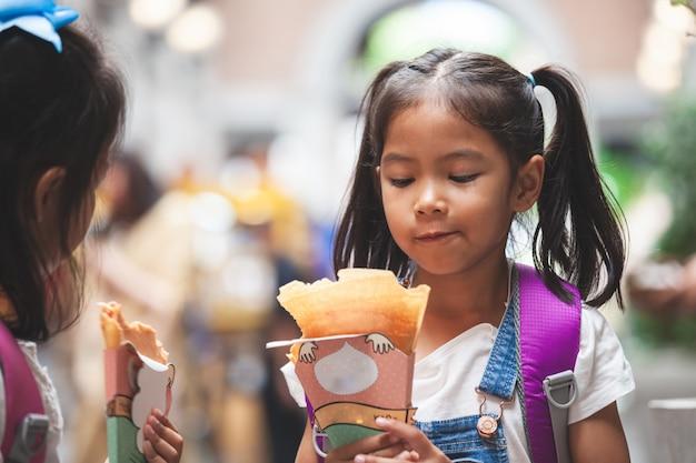 Twee leuke aziatische kindmeisjes die met rugzak pannekoek samen na school in de school eten Premium Foto