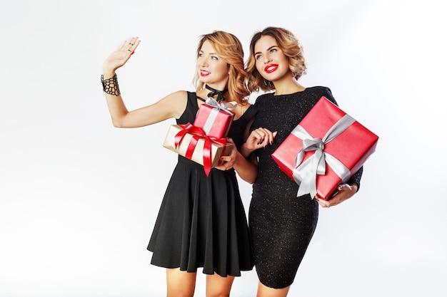 Twee leuke vieren vrouw met grote nieuwe jaar geschenkdozen. verras gezichten. het dragen van een elegante zwarte jurk. Gratis Foto