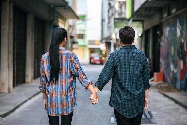 Twee liefdevolle vrouwen staan en hand in hand op straat. Gratis Foto