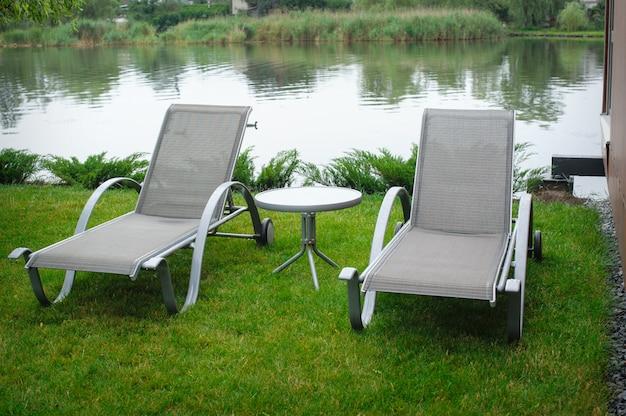 Twee ligstoelen aan de oever van de rivier Premium Foto