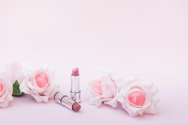 Twee lippenstiften en mooie rozen op roze achtergrond Gratis Foto