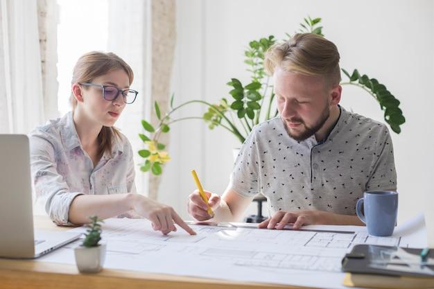 Twee mannelijke en vrouwelijke architect die aan blauwdruk op het kantoor werken Gratis Foto