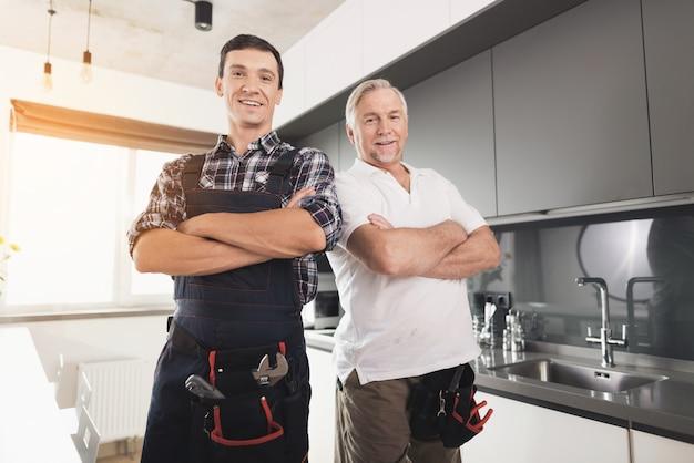 Twee mannelijke loodgieters poseren in de keuken. wapens akimbo. Premium Foto