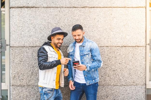 Twee mannelijke vrienden die mobiele telefoon in openlucht met behulp van terwijl het glimlachen. Premium Foto