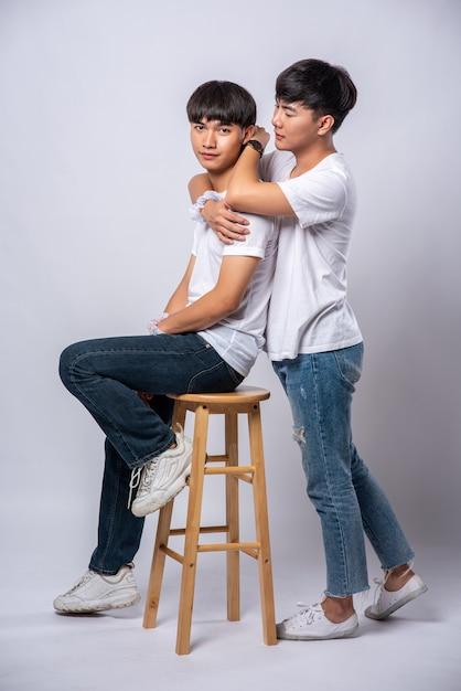 Twee mannen die van elkaar houden, knuffelen en zitten op een stoel. Gratis Foto