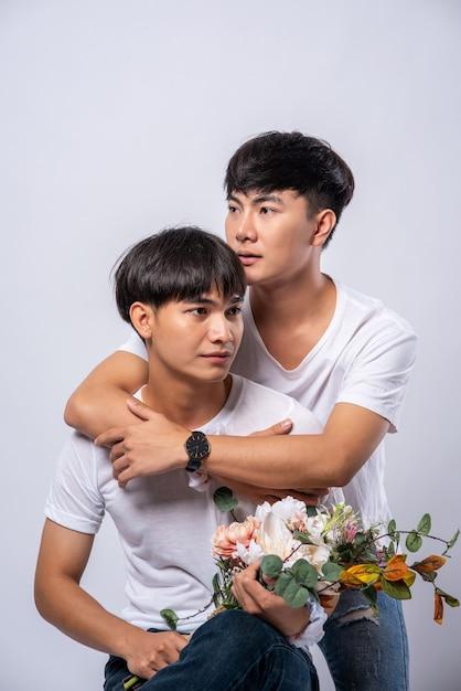 Twee mannen die van elkaar houden, knuffelen van achter elkaar. Gratis Foto