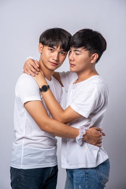 Twee mannen die van elkaar houden omhelzen elkaar vrolijk. Gratis Foto