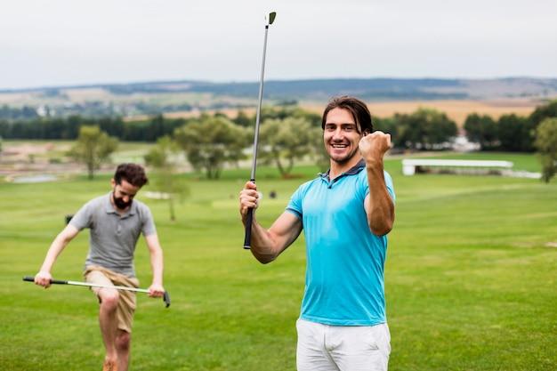 Twee mannen plezier op golfbaan Gratis Foto