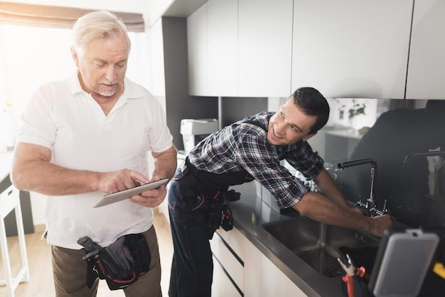 Twee mannen van loodgieters staan in de keuken Premium Foto